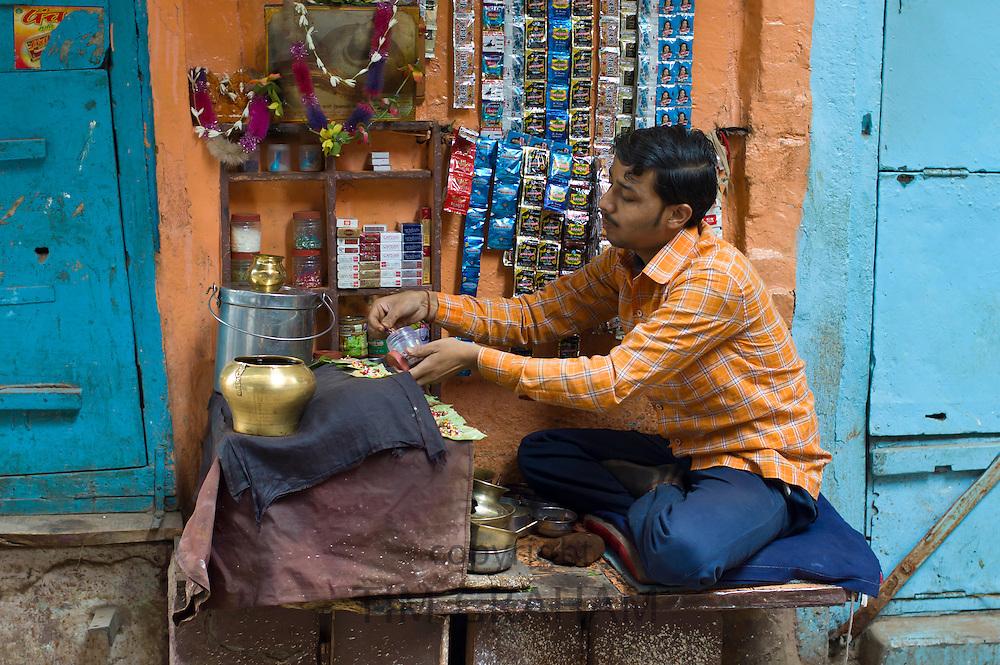 Indian man runs market stall in alleyway in the city of Varanasi, Benares, Northern India