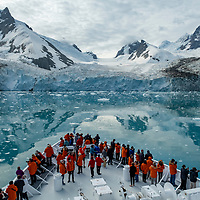 Guests gather on the bow of the National Geographic Orion in front of the Risting Glacier in Dygalski Fjord on South Georgia Island.