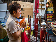 "29 JUNE 2015 - BANGKOK, THAILAND:  A Thai civil servant prays at a Buddhist ""spirit house"" in the Bang Chak Market in Bangkok. The Bang Chak Market serves the community around Sois 91-97 on Sukhumvit Road in the Bangkok suburbs. About half of the market has been torn down, vendors in the remaining part of the market said they expect to be evicted by the end of the year. The old market, and many of the small working class shophouses and apartments near the market are being being torn down. People who live in the area said condominiums are being built on the land.    PHOTO BY JACK KURTZ"