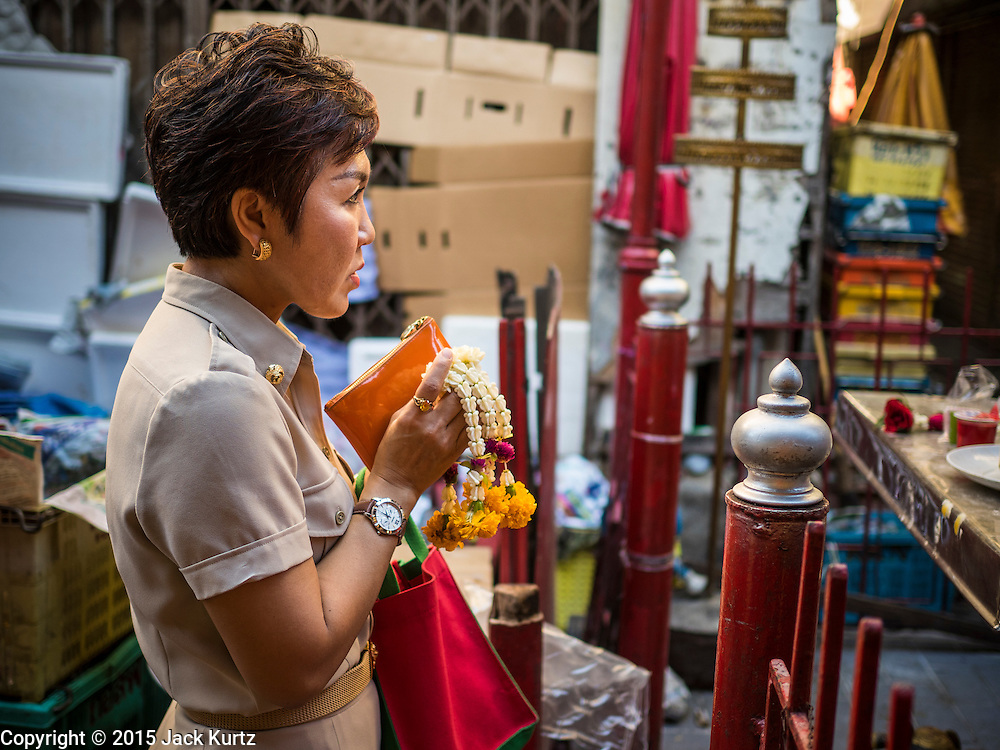 """29 JUNE 2015 - BANGKOK, THAILAND:  A Thai civil servant prays at a Buddhist """"spirit house"""" in the Bang Chak Market in Bangkok. The Bang Chak Market serves the community around Sois 91-97 on Sukhumvit Road in the Bangkok suburbs. About half of the market has been torn down, vendors in the remaining part of the market said they expect to be evicted by the end of the year. The old market, and many of the small working class shophouses and apartments near the market are being being torn down. People who live in the area said condominiums are being built on the land.    PHOTO BY JACK KURTZ"""