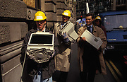 City workers carry office possessions including computer hard drives and files that were damaged by the IRA bomb that devastated the City of Londons Bishopsgate area in 1993, on 26th April 1993, in London, England. Allowed to return to their desks to recover their data and working paperwork, they walk through the ancient streets en route to new emergency office elsewhere in the capital. The Irish Republican Army IRA exploded a truck bomb on Bishopsgate. Buildings up to 500 metres away were damaged with one and a half million square feet 140,000 m of office space being affected and over 500 tonnes of glass broken. Repair costs reached approx £350 million. It was said that Roman remains could be viewed at the bottom of the pit the bomb created. One person was killed when the one ton fertiliser bomb detonated directly outside the medieval St Ethelburgas church.