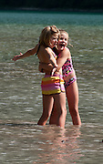 Girls in swim suits play in Avalanche Lake, Glacier National Park, Montana, USA