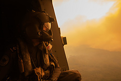 Royal Australian Navy Aircrewman Leading Seaman Ben Nixon of 808 Squadron, assesses the Tianjara Fire in the Moreton and Jerrawangala National Parks out of an MRH90 Taipan Military Support Helicopter.