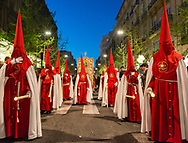 A brotherhood in bright red robes walks the street of Granada just after sunset, in one of the processions of the Holy Week. Andalusia, Spain