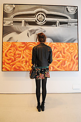 © Licensed to London News Pictures. 21/10/2013. London, UK. A woman views I Love You with My Ford by James Rosenquist at The Pop Art Design Exhibition preview at The Barbican Centre. Photo credit : David Mirzoeff/LNP