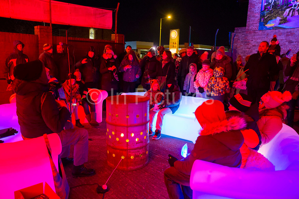 A man playing the accordion as part of the 'Oil Drum Sessions' by Rob Hancox and Friends at the Cheriton Light Festival 2018 on Cheriton High Street, Folkestone, Kent, United Kingdom. The festival is deemed the most spectacular free winter event in Kent, and attracts thousands of visitors every year.