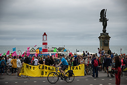 """© Licensed to London News Pictures . 22/09/2019. Brighton, UK. Environmental campaigners from Extinction Rebellion highlight the climate emergency and deploy a large red and white lighthouse lightship named """" Greta """" , on Brighton Promenade , during the second day of the 2019 Labour Party Conference from the Brighton Centre . Photo credit: Joel Goodman/LNP"""