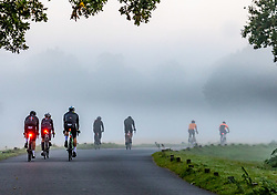 Licensed to London News Pictures. 22/09/2021. Surrey, UK. Cyclists enjoy a misty morning on the first day of Autumn in Richmond Park, south-west London today as weather forecasters predict warm autumnal weather for the next 7 days with highs of 24c. Photo credit: Alex Lentati/LNP