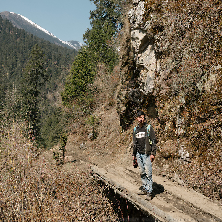 Young men coming down from Laya, wearing Supreme brand T-shirt. From the end of the dirt road, it takes 7 hours to trek up to Laya village.