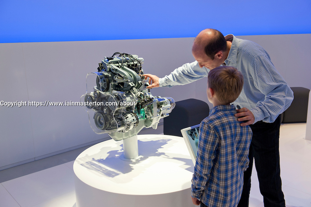 Father showing son how engine works at the  Paris Motor Show 2010