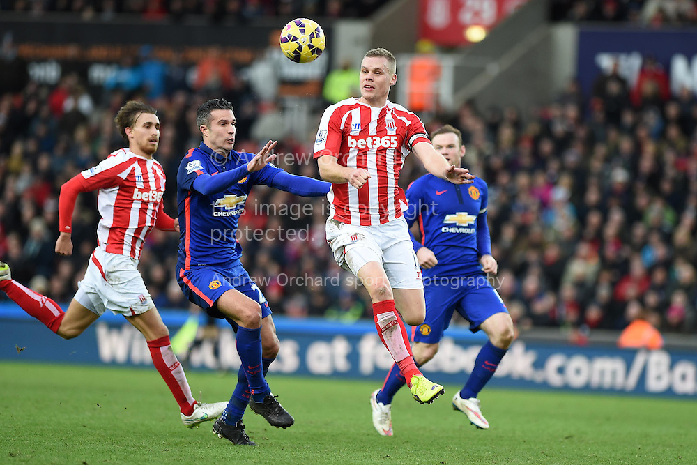 Ryan Shawcross of Stoke city ® heads clear from Robin Van Persie of Man Utd. Barclays Premier league match, Stoke city v Manchester Utd at the Britannia Stadium in Stoke on Trent, Staffs on New Years Day , Thursday 1st Jan 2015. pic by Andrew Orchard. Andrew Orchard sports photography.