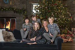 woman with her children by a Christmas tree