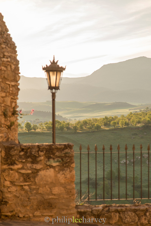 View of hills and fields behind railing at sunrise, Ronda, Andalusia, Spain
