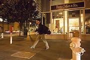 Een man loopt 's avonds door San Francisco langs een koffietentje.<br /> <br /> A man is passing a coffee bar in San Francisco in the evening.