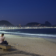 Praia de Copacabana at dusk. A women reads a book on a beachside bench at Copacabana beach, one of the world's most famous urban beaches. The beach and hotel strip stretches for 1.5 miles (4km) from the Morro do Leme at the Northern end, to Arpoador at the South. Copacabana beach, Rio de Janeiro,  Brazil. 12th August 2010. Photo Tim Clayton.