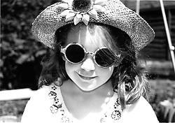 Portrait of young girl wearing hat and sunglasses smiling,