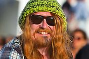 Glastonbury Festival, 2015. Shangri La, happy, male, crusty festival goer with long hair and a beanie hat