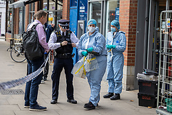 Licensed to London News Pictures. 26/08/202. London, UK. Police forensics bag up sliced meats at a Local Tescos supermarket in Fulham, southwest London this today after a man was arrested for contaminating food with syringes at three supermarkets last night. Tescos, Sainsbury's and a Waitrose on the Fulham Palace Road in London have been closed with forensic teams checking food stocks. Police have urged anyone who bought food on Wednesday evening at one of the stores to dispose of it as soon as possible. Photo credit: Alex Lentati/LNP