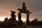 """Inukshuk (stone marker) above the town of Iqaluit, Nunavut, Canada. Iqaluit, with population of 6,000, is the largest community in Nunavut as well as the capital city. It is located in the southeast part of Baffin Island. Formerly known as Frobisher Bay, it is at the mouth of the bay of that name, overlooking Koojesse Inlet. """"Iqaluit"""" means 'place of many fish'. The image is part of a collection of images and documentation for Hungry Planet 2, a continuation of work done after publication of the book project Hungry Planet: What the World Eats, by Peter Menzel & Faith D'Aluisio."""