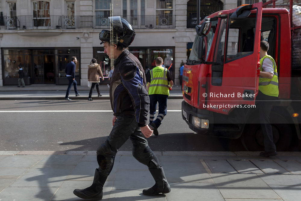 Motorcyclist wears his helmet balanced on his head, on 30th March 2017, in London, England.