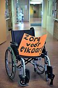 Nederland, Millingen, 12-12-2017In een zorgcentrum voor ouderen staat een rolstoel met daarin een bord, protestbord met de tekst : zorg voor elkaar.Het is erin gezet door stakende onderwijzers die hun stakingsdag uit solidariteit invullen met het helpen van het personeel in het tehuis.Foto: Flip Franssen