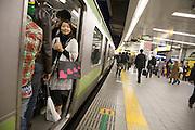 smiling girl in train door opening Tokyo Japan