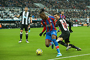 Wilfried Zaha (#11) of Crystal Palace dribbles the ball beyond Javi Manquillo (#19) of Newcastle United during the Premier League match between Newcastle United and Crystal Palace at St. James's Park, Newcastle, England on 21 December 2019.