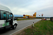 Tourist bus stopped at stop-sign for aeroplane. Near Zadar, Croatia