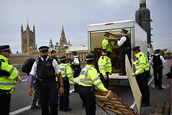 © Licensed to London News Pictures. 07/10/2019. London, UK. A van is seized by police as Extinction Rebellion (XR) activists are arrested on Westminster Bridge after bolting themselves to street furniture and makeshift obstacles. Photo credit: Guilhem Baker/LNP