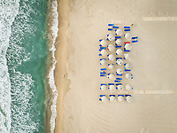 Aerial view of empty sunbeds and parasols on beach, Greece.