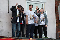 © Licensed to London News Pictures . 10/06/2015 . Manchester , UK . People believed to be Dominic Doyle's family stand on a ledge above a pizza shop and are cheered by the crowd . A vigil in memory of Dominic Doyle , near to where he was found fatally stabbed on Sunday morning (7th June 2015) , on Manchester Road in East Manchester . The Manchester Road (A57) is closed to traffic as hundreds gather to remember the 21 year old . Three people have been charged in connection with Doyle's murder and a 16 year old has been arrested on suspicion of murder . Photo credit : Joel Goodman/LNP