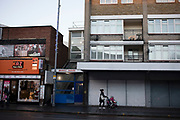 Street scene with a woman pushing a pram past boarded up shops and council flats on a wet day in Leytonstone in East London, United Kingdom. Leytonstone is an area of East London, and part of the London Borough of Waltham Forest.