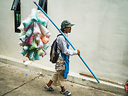 12 SEPTEMBER 2016 - BANGKOK, THAILAND:  A cotton candy vendor walks to the mosque during the celebration of Eid al-Adha at Haroon Mosque in Bangkok. Eid al-Adha is also called the Feast of Sacrifice, the Greater Eid or Baqar-Eid. It is the second of two religious holidays celebrated by Muslims worldwide each year. It honors the willingness of Abraham to sacrifice his son, as an act of submission to God's command. Goats, sheep and cows are sacrificed in a ritualistic manner after services in the mosque. The meat from the sacrificed animal is supposed to be divided into three parts. The family retains one third of the share; another third is given to relatives, friends and neighbors; and the remaining third is given to the poor and needy.         PHOTO BY JACK KURTZ