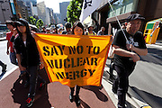 """Anti nuclear protesters carrying  a flag reading, """"say no to nuclear energy"""" during a protest march in Tokyo, Japan Sunday June 2nd 2013"""