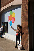 A young woman standing next to a Barclays Bank seemingly holds a bunch of multicoloured balloons. In a scene of misleading visual information, we think we see the girl's arm outstretched but realise it is the arm of a person in the advert behind - a visual corruption of the facts. In the background is a woman leaning into a Barclays bank cash dispenser