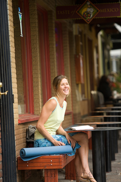 Young woman laughing at table. Portland, OR.