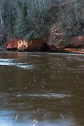 Reddish sandstone cliffs on side of Ķūķu iezis and dark brown waters of River Gauja on snowless winter day, Gauja National Park (Gaujas Nacionālais parks), Latvia Ⓒ Davis Ulands | davisulands.com