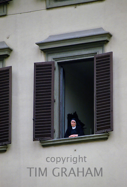 Catholic nun stands at a window in the Vatican, Vatican City State