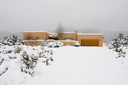 Wide view of new adobe home in snow, Taos, New Mexico