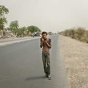 Ravi talked very quietly, like he was afraid to be loud. He said yes to my offer of water. He didn't want anything else. I put the bottle next to him on the road and he looked up. He had scars on his belly. It seems that most of these highway walkers are ghosts to the passersby. <br /> Uttar Pradesh Province.