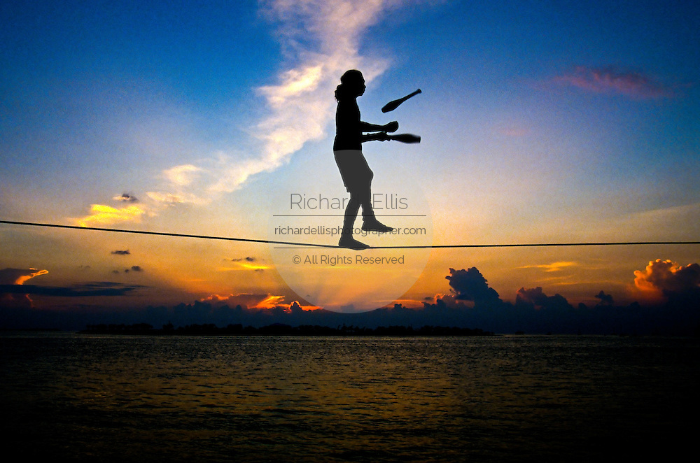 A tightrope walker performs during the sunset celebration at Mallory Square in Key West Florida.