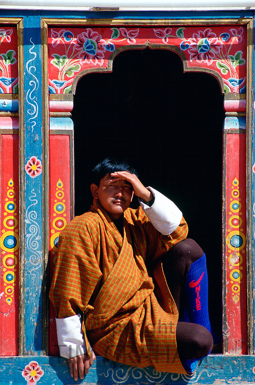 Bhutanese man shielding his eyes from the sun as he sits in an ornate carved and decorated window.  His modern Nike sports socks contrast with his traditional outfit, Paro, Bhutan