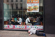 Diners ignore a man lying unconscious outside a McDonalds restaurant on a London street. As people get on with eating their burgers and fries such as illustrated in the window poster above their heads, the unfortunate man is horizontal on the pavement (sidewalk). He may be homeless or simply suffering from the effects of afternoon alcohol. The scene is almost Dickensian where the drunk were treated with disdain as they lay pitifully on London's streets, the outcasts of a socially-divided Britain.