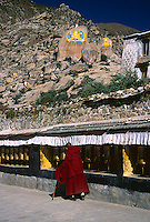 A monk slowly makes his way around the kora of Drepung Monastery, Lhasa, Tibet.