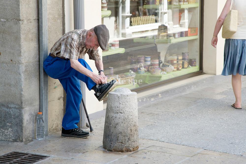 elderly man tying his shoe laces