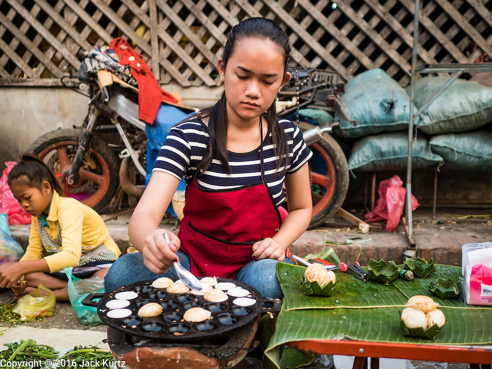 """13 MARCH 2016 - LUANG PRABANG, LAOS: A woman makes grilled quail eggs, an Asian delicacy, in the market in Luang Prabang. Luang Prabang was named a UNESCO World Heritage Site in 1995. The move saved the city's colonial architecture but the explosion of mass tourism has taken a toll on the city's soul. According to one recent study, a small plot of land that sold for $8,000 three years ago now goes for $120,000. Many longtime residents are selling their homes and moving to small developments around the city. The old homes are then converted to guesthouses, restaurants and spas. The city is famous for the morning """"tak bat,"""" or monks' morning alms rounds. Every morning hundreds of Buddhist monks come out before dawn and walk in a silent procession through the city accepting alms from residents. Now, most of the people presenting alms to the monks are tourists, since so many Lao people have moved outside of the city center. About 50,000 people are thought to live in the Luang Prabang area, the city received more than 530,000 tourists in 2014.    PHOTO BY JACK KURTZ"""
