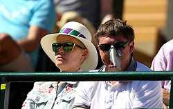 A spectator shields himself from the sun as he watches the action on day One of the Wimbledon Championships at the All England Lawn Tennis and Croquet Club, Wimbledon.