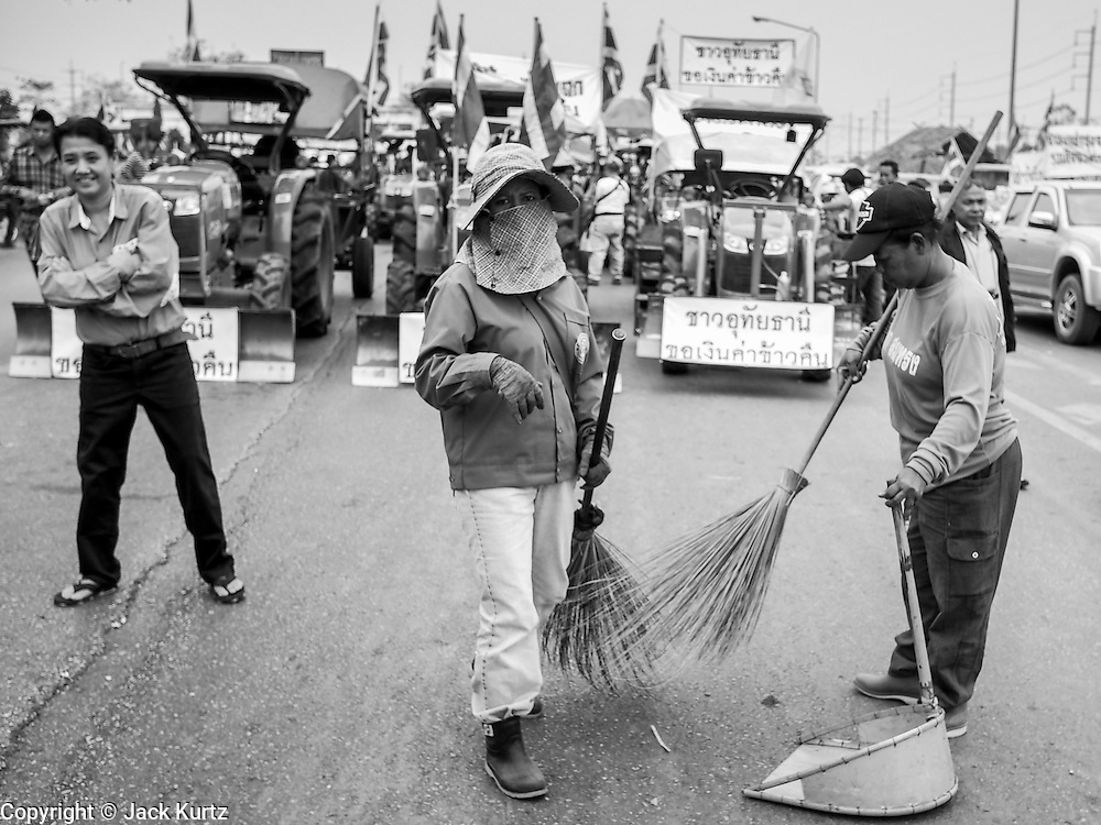 21 FEBRUARY 2014 - KHLONG CHIK, PHRA NAKHON SI AYUTTHAYA, THAILAND:  Women clean the highway after a protest by farmers. About 10,000 Thai rice farmers, traveling in nearly 1,000 tractors and farm vehicles, blocked Highway 32 near Bang Pa In in Phra Nakhon Si Ayutthaya province. The farmers were traveling to the airport in Bangkok to protest against the government because they haven't been paid for rice the government bought from them last year. The farmers turned around and went home after they met with government officials who promised to pay the farmers next week. This is the latest blow to the government of Yingluck Shinawatra which is confronting protests led by anti-government groups, legal challenges from the anti-corruption commission and expanding protests from farmers who haven't been paid for rice the government bought.   PHOTO BY JACK KURTZ