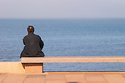A man in black sitting on a red stone bench faxing the river sea, on the riverside seaside walk along the river Rio de la Plata Ramblas Sur, Gran Bretagna and Republica Argentina Montevideo, Uruguay, South America