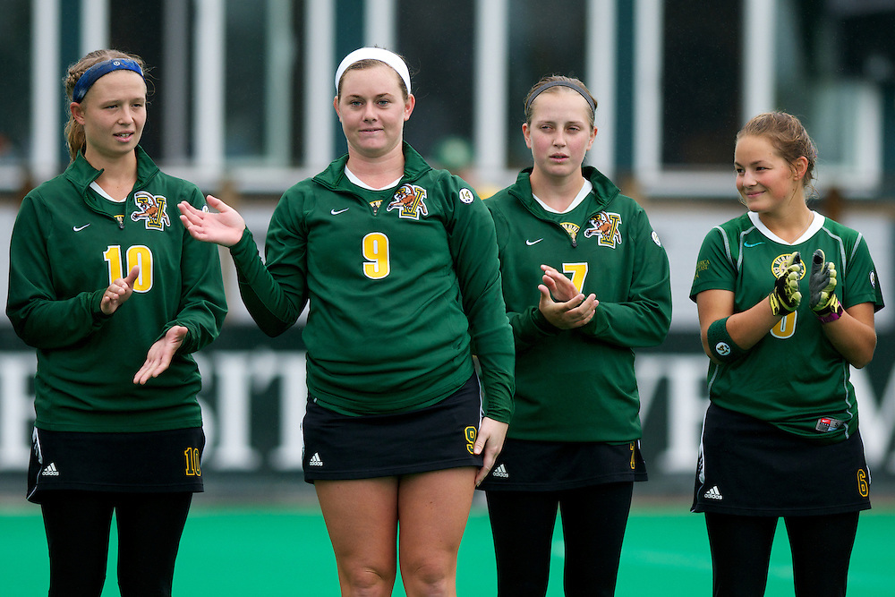 Catamounts forward Colleen Slaughter (9) waves to the crowd as Catamounts defenseman Jackie Bendick (10), Catamounts midfielder Kalla Gervais (7) and Catamounts forward Taylor Silvestro (6) look on during the player introductions before the start of the women's field hockey game between the Maine Black Bears and the Vermont Catamounts at Moulton/Winder Field on Saturday afternoon September 29, 2012 in Burlington, Vermont.